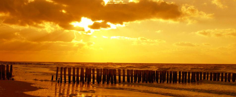 strand met paaltjes en mooie lucht
